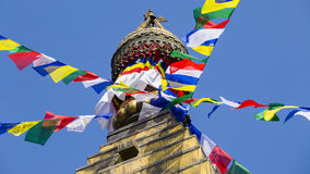 Prayer colorful flags flying from the Buddhist Stupa, a place of holy worship.  Temple in the Kathmandu valley, Nepal Royalty Free Stock Photo