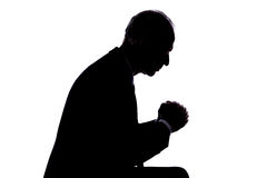 Prayer concept. Silhouette of a man expressing prayer Stock Image