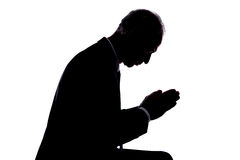 Prayer concept. Silhouette of a man expressing prayer Stock Images