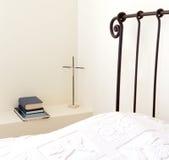 Prayer corner. Metall cross with wooden Jesus and  book stack in the bedroom Stock Image