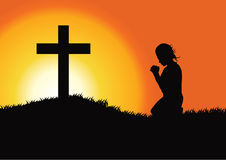 Prayer at the Cross. Silhouette of a woman praying under the cross Stock Photography