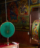 Prayer drum and wall paintings in the buddhist temple Royalty Free Stock Images