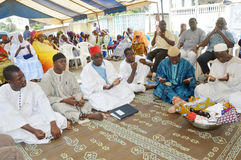 Prayer of the end of the ceremony. Abidjan, Ivory Coast - February 26, 2015: Religious leaders are doing the last prayer to bless the newlyweds. Sitting on mats Stock Images