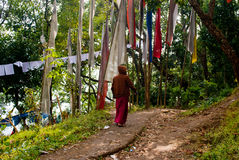 Prayer flag. A Buddhist monk is walking in a forest way beside Prayer MANTRAS flag OM Mani Padme HUM hang along a monastery path in Sikkim, India. Traditionally Royalty Free Stock Photos