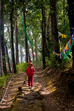 Prayer flag. A Buddhist student monk is walking in a forest way beside Prayer MANTRAS flag OM Mani Padme HUM hang along a monastery path in Sikkim, India Stock Images