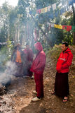Prayer flag. A group of Buddhist student monks are warming themselves with fire in a forest way beside Prayer MANTRAS flag OM Mani Padme HUM hang along a Royalty Free Stock Images