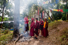 Prayer flag. A group of Buddhist student monks are warming themselves with fire in a forest way beside Prayer MANTRAS flag OM Mani Padme HUM hang along a Stock Image