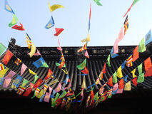 Prayer flags on Chinese temple. Traditional colorful prayer flags attached to rooftop of Chinese temple Stock Image