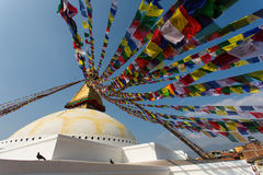 Prayer flags flying against the sun from the Boudhanath Stupa - symbol Kathmandu, Nepal Stock Photo