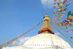 Prayer flags flying over Bodhnath Stupa, Asia's largest stupa.  Royalty Free Stock Images