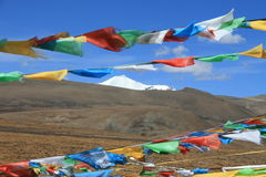 Prayer flags flying over snow mountain on Tibetan Plateau.  Stock Photos
