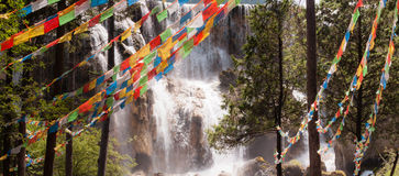 Prayer flags in front of the waterfall Stock Photos