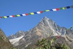 Prayer flags in Nepal trekking at Himalaya mountains. Tibetan colorful prayer flags in Nepal trekking at Himalaya mountains snow summits royalty free stock photo