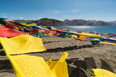 Prayer flags at Pangong Lake.Blur on foregroud. Pangong Tso, Tibetan for long, narrow, enchanted lake, also referred to as Pangong Lake, is an endorheic lake in Stock Image