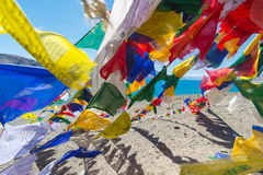 Prayer flags at Pangong Lake.Blur on foregroud. Pangong Tso, Tibetan for long, narrow, enchanted lake, also referred to as Pangong Lake, is an endorheic lake in Stock Photo