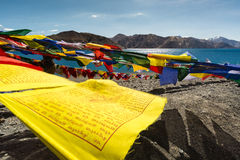 Prayer flags at Pangong Lake.Blur on foregroud. Pangong Tso, Tibetan for long, narrow, enchanted lake, also referred to as Pangong Lake, is an endorheic lake in Royalty Free Stock Images