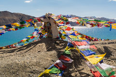 Prayer flags at Pangong Lake in Ladakh,India. Pangong Tso, Tibetan for long, narrow, enchanted lake, also referred to as Pangong Lake, is an endorheic lake in Stock Image
