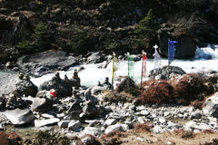 Prayer flags and prayer stones along river, Sikkim Stock Photography