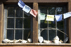 Prayer flags, rock collection and old fashioned window panes Royalty Free Stock Photos