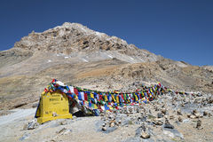 Prayer flags and stone pyramids at the foot of jagged mountain Royalty Free Stock Photos