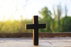 Cross on a wood background . Cross against the sky . Prayer hands and cross . Light cross of Christ . Walk to the cross . Sunbeams and cross . Sunset Man of royalty free stock images