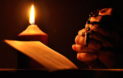 Prayer hands with crucifix. Still life with candle, prayer book and prayer hands Stock Image