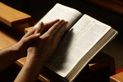 Prayer. Hands on Holy Bible in prayer at church royalty free stock photo