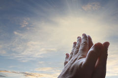 Prayer. Hands together praying in bright sky Royalty Free Stock Photography