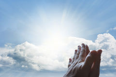 Prayer. Hands together praying in bright sky Stock Images