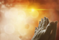 Prayer. Hands together praying in front of bright background. Copy space Stock Photography