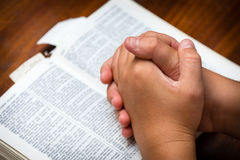 Prayer Hands. A young boy clasping hands together in prayer over the bible royalty free stock photography