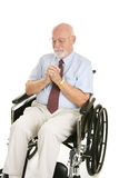 Prayer for Healing. Senior man in wheelchair prays to recover his health.  Isolated on white Royalty Free Stock Photo