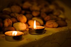 Prayer and hope concept. Retro candle light and old stone with l. Ighting effect and glitter abstract background with bokeh defocused lights Royalty Free Stock Photography