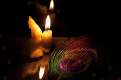Prayer and hope concept . Retro candle light with peacock feather eye. Vintage image stock photos