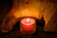 Prayer and hope concept. Retro pink candle light in crystal glas. S and old wooden Royalty Free Stock Photo