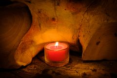 Prayer and hope concept. Retro pink candle light in crystal glas. S and old wooden Stock Photography