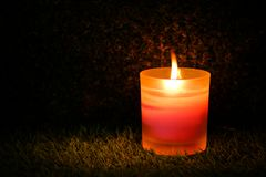 Prayer and hope concept. Retro pink candle light in crystal glass stock photo