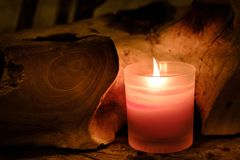 Prayer and hope concept. Retro pink candle light in crystal glass and old wooden royalty free stock photo