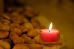 Prayer and hope concept. Retro pink candle light and old stone w royalty free stock photos