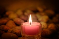 Prayer and hope concept. Retro pink candle light and old stone w stock photos