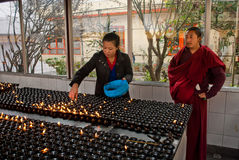 Prayer lights. A young lady is lighting the lamps under supervision of a student monk at prayer room of Dro-dul Chorten stupa in Gangtok, Sikkim, Indian Stock Photography