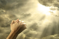 Prayer raised hands on the sky. Closeup of prayer raised hands on the sky with bright rays from the cloud Royalty Free Stock Images