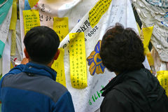 Prayer ribbons at Freedom Bridge, between North and South Korea. Two koreans look at the memorial prayer ribbons on display at the Korean border Royalty Free Stock Image