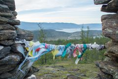 Prayer ribbons on top of the hillock dedicated to a local Tutelary deity. Siberia, Russia royalty free stock images