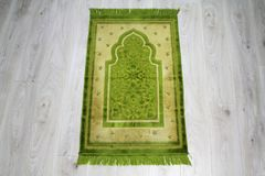 Prayer rug for muslims. Prayer rug for muslims in green colour Stock Photo