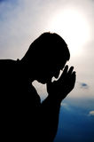 Prayer silhouette. Praying man with blue sky on background. Silhouette Stock Image