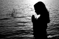 Prayer Silhouette. A beautiful background with a silhouette of an Indian woman praying by the river Royalty Free Stock Image