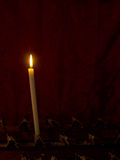 Prayer. Single church candle burns in front of red curtain. Memo royalty free stock photos