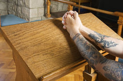Prayer time. Tattooed arms in prayer pose inside church Royalty Free Stock Image