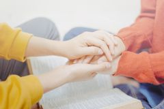 Prayer together on holy bible. Mentor holding hands encouraged and prayer together. on the holy bible stock photography